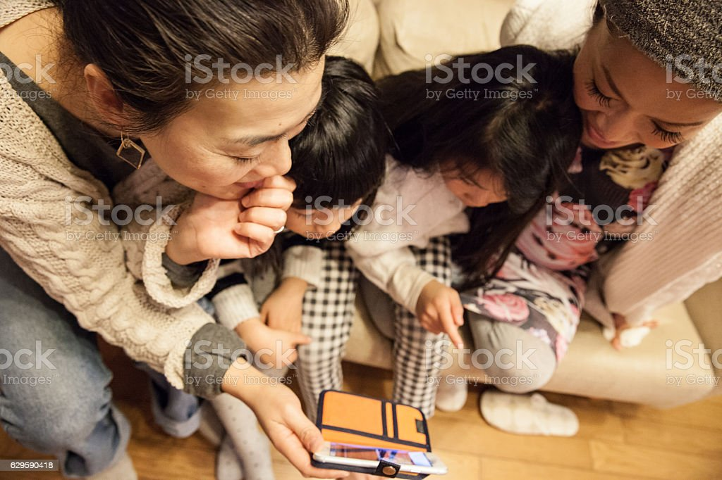Japanese pregnant mother, daughter, friends watching at smartphone stock photo