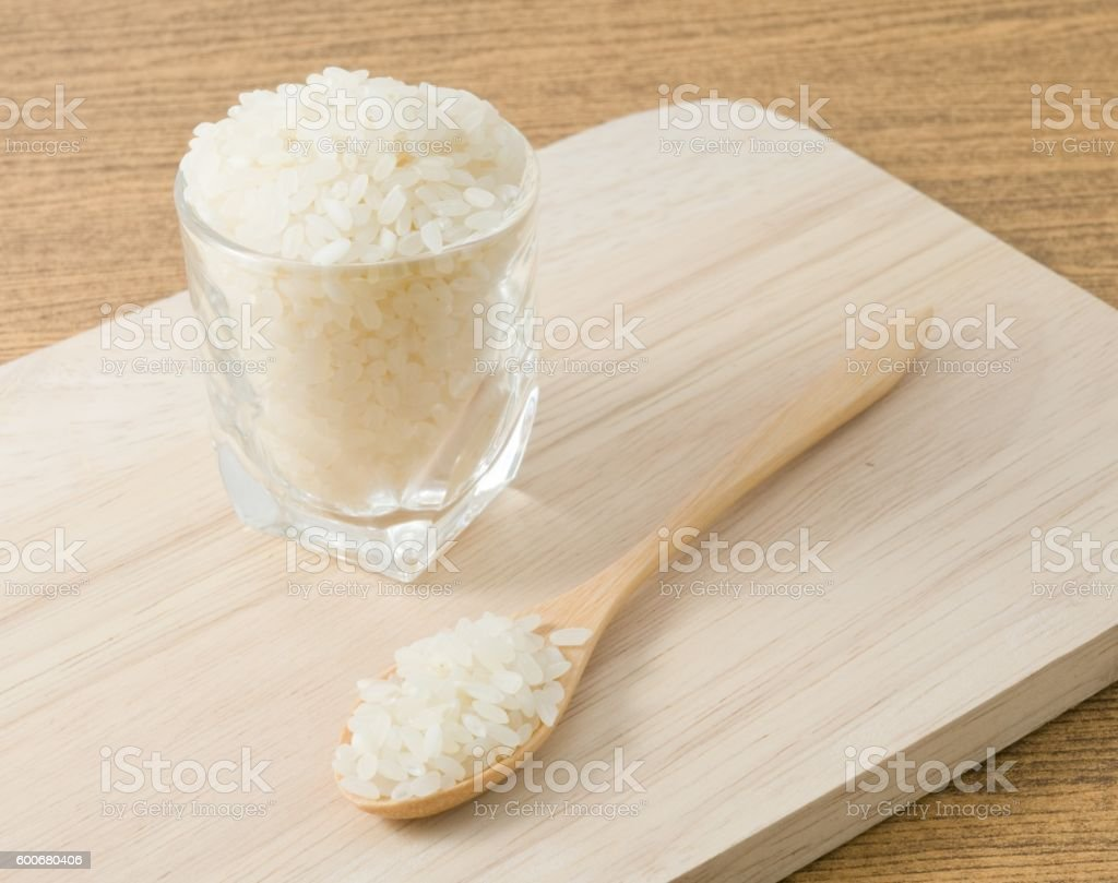 Japanese Rice in Wooden Spoon and Glass Cup stock photo
