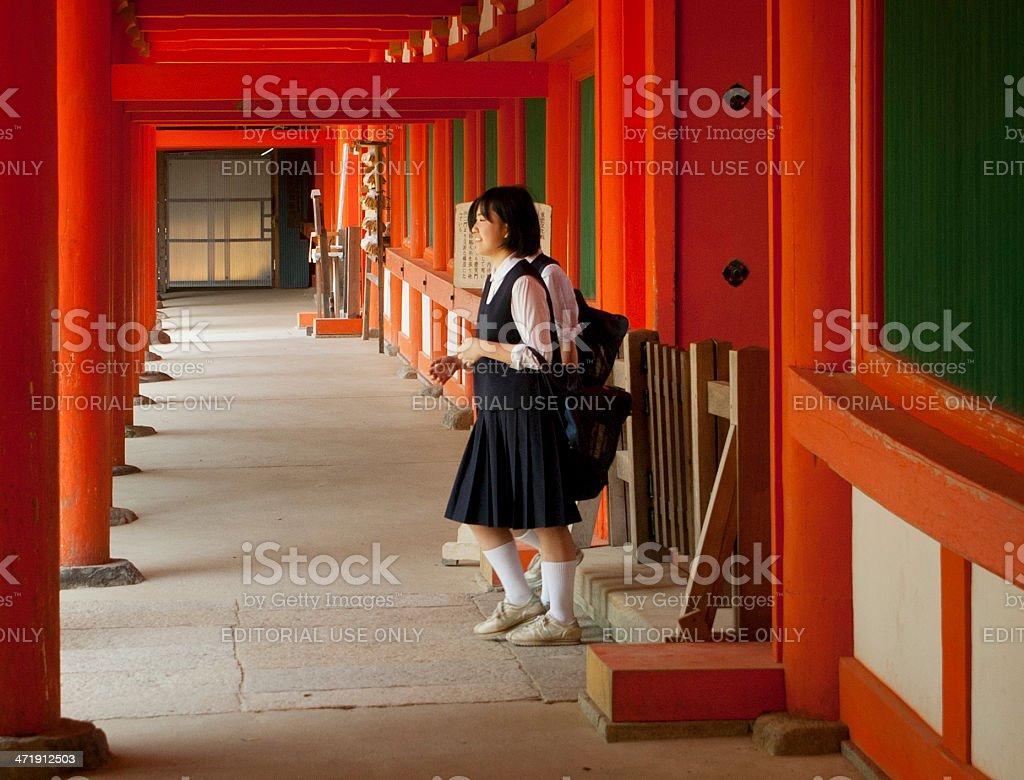 Japanese schoolgirls at Shinto shrine (Kasuga Taisha) royalty-free stock photo