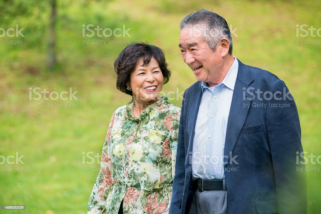 Japanese senior couple hiking in the park stock photo