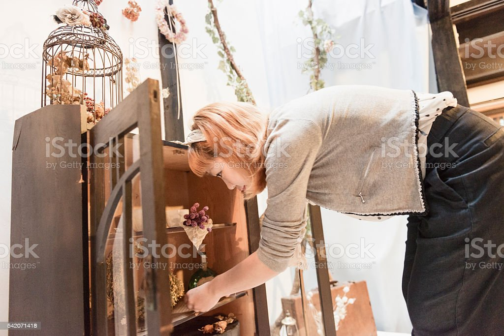 Japanese Shop Owner Arranging Retail Display in Kyoto Store stock photo