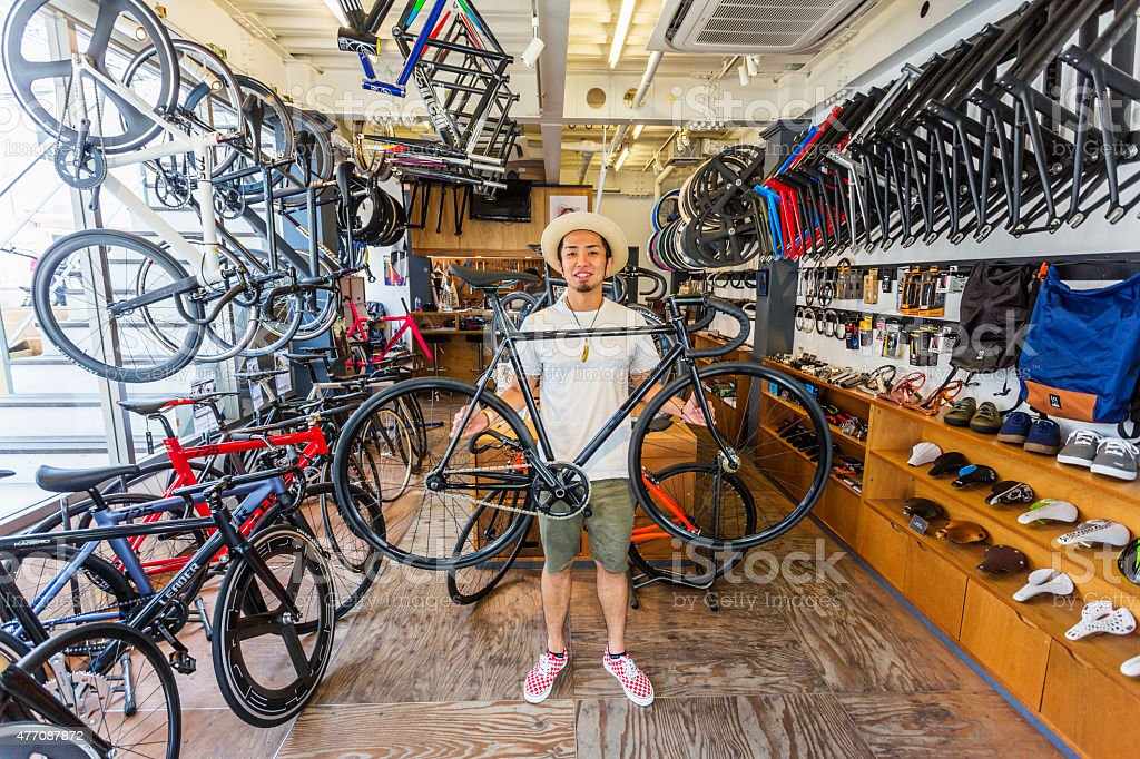 Japanese Small Businessman Holding a Bicycle in his Bike Shop stock photo