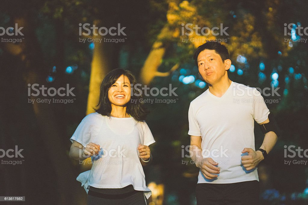 Japanese Sport Couple Exercising Outdoors In The Early Morning stock photo