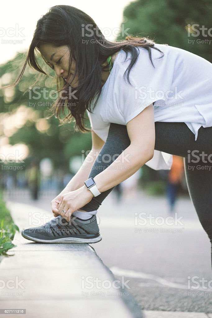 Japanese sport woman tying her shoelaces during daily workout stock photo