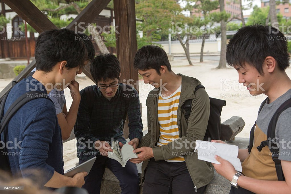 japanese student classmates checking books at street in kyoto japan stock photo
