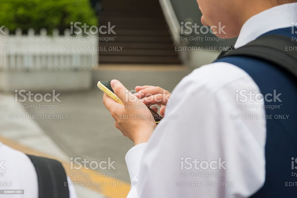 Japanese Student Texting on Mobile Phone Outdoors Nagoya Japan stock photo