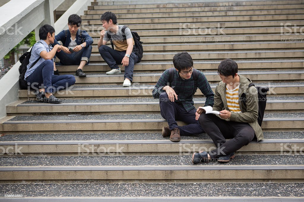 japanese students sitting and talking at stairs in kyoto japan stock photo