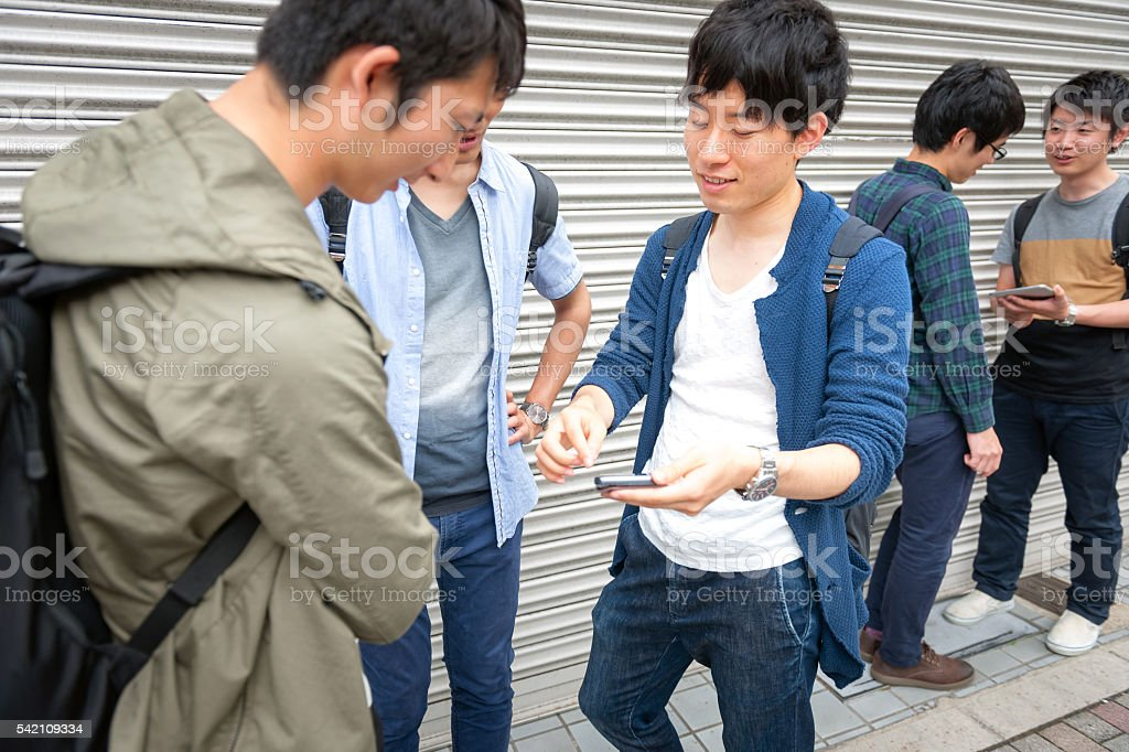 Japanese students together with friend checking telephone in Kyoto,Japan stock photo