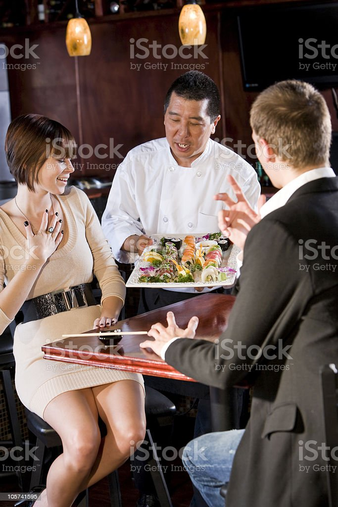 Japanese sushi restaurant, chef serving customers royalty-free stock photo