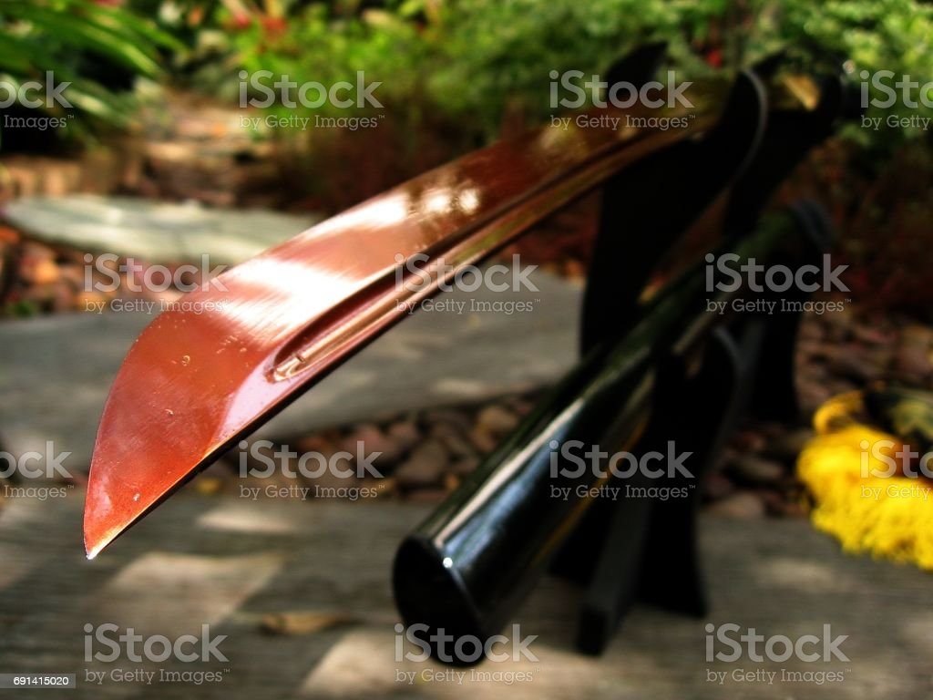 Japanese sword on stand in garden background stock photo