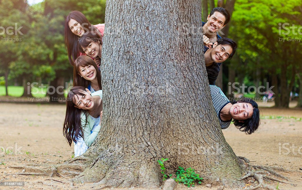 Japanese teenagers peeking out from behind a tree, Tokyo. stock photo