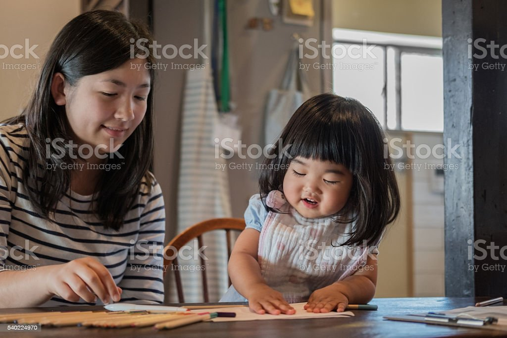 Japanese Toddler and Teenaged Girl Drawing and Playing with Paper stock photo