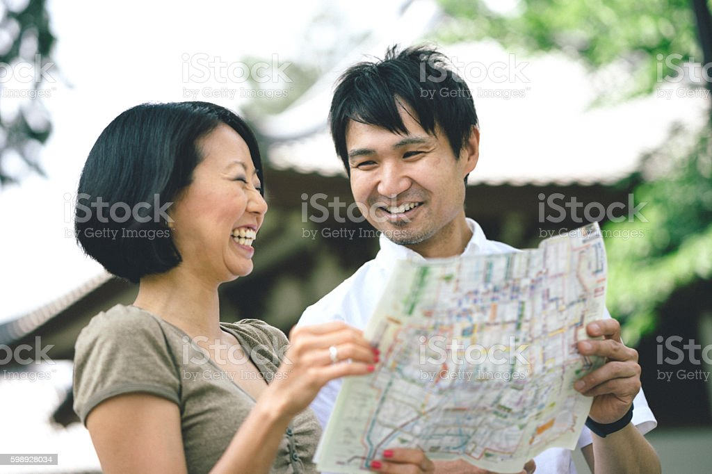 Japanese tourist couple visiting Kyoto looking at map stock photo