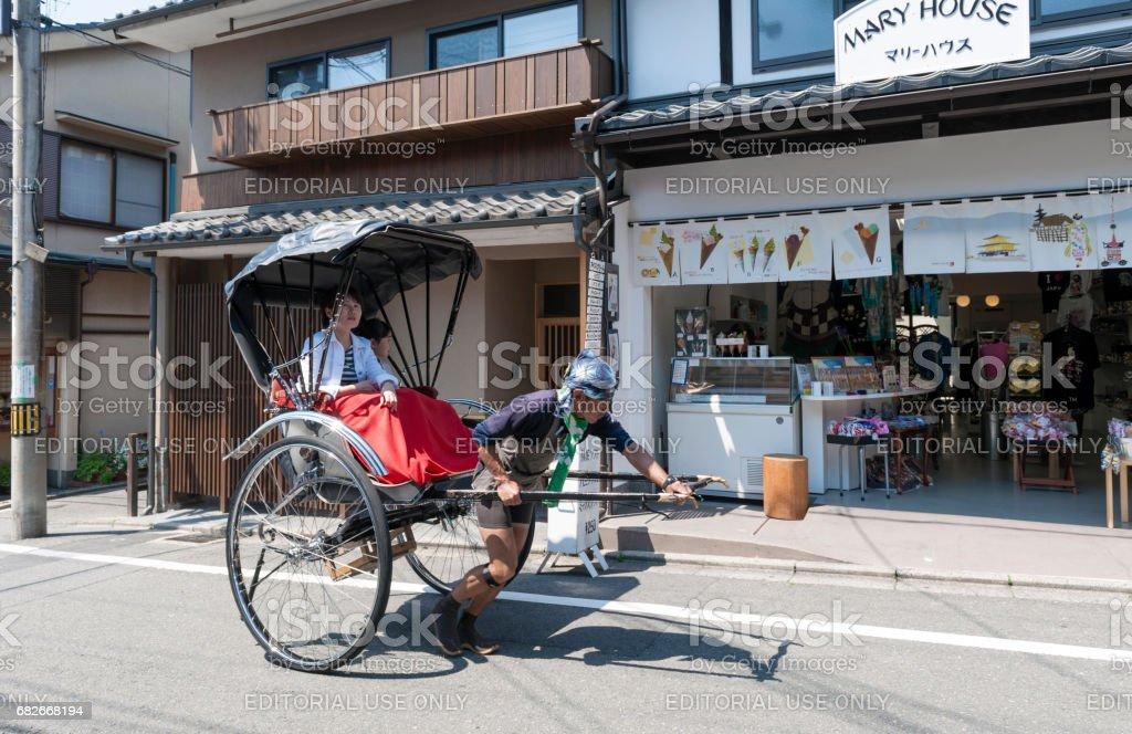Japanese traditional hand pulled rickshaw carrying tourists on Matsubara street in Kyoto, Japan stock photo
