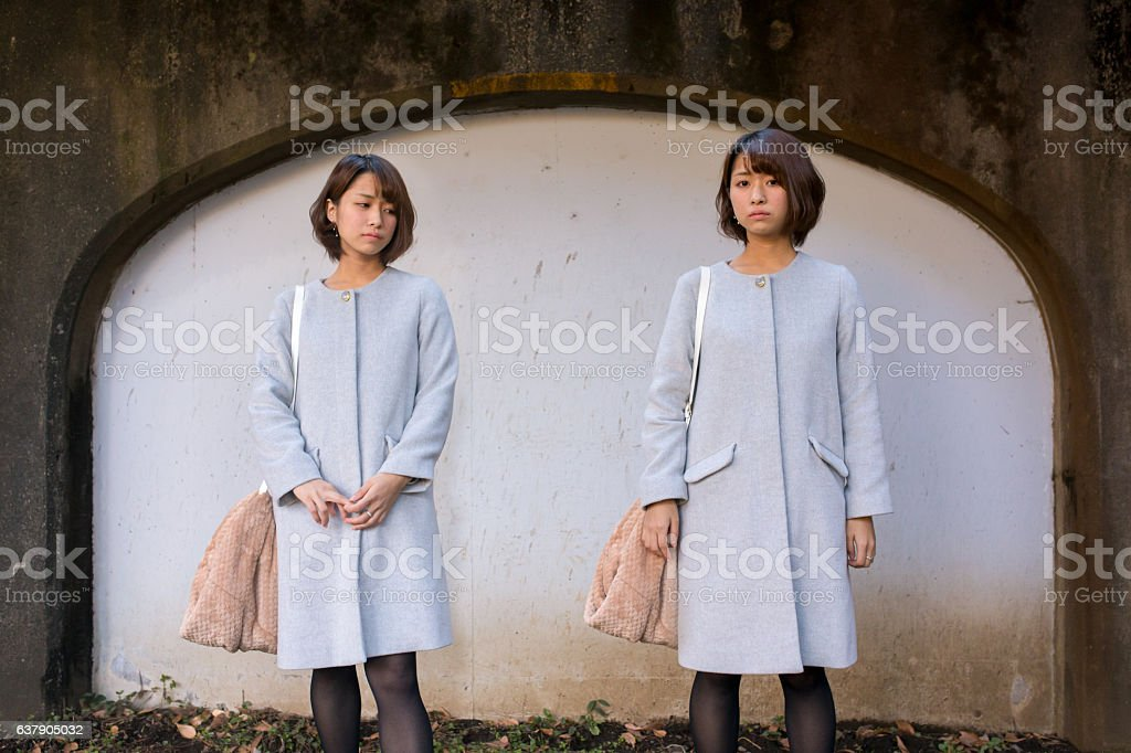 Japanese twin sisters standing in front of wall stock photo