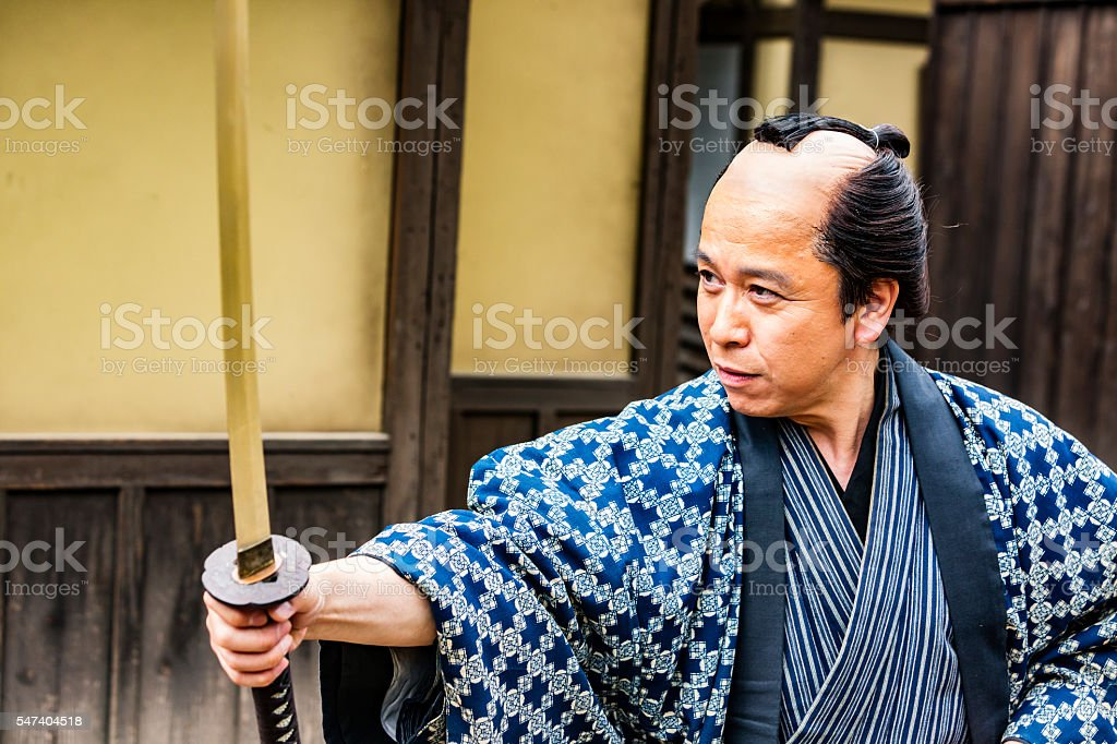 Japanese Warrior Drawing His Samurai Sword Katana stock photo
