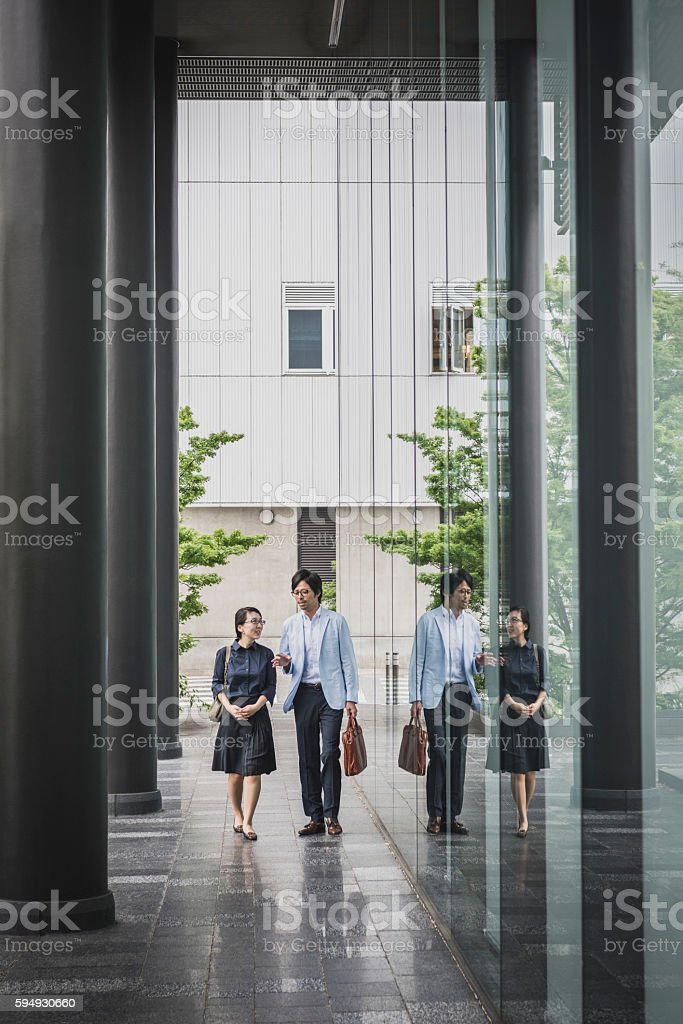 Young businesswoman and mid adult man outside building with...