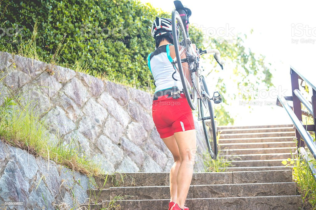 Japanese Woman Carrying Bike on Shoulders in Kyoto City, Japan stock photo
