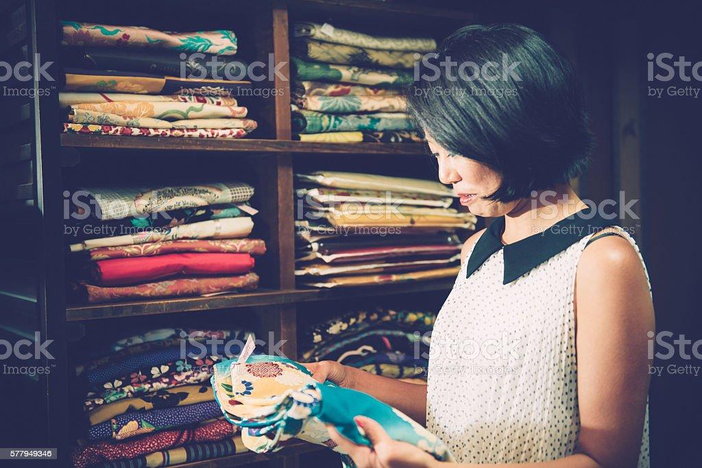 Japanese Woman Choosing Blue Floral Fattern Kimono in Kyoto, Japan stock photo