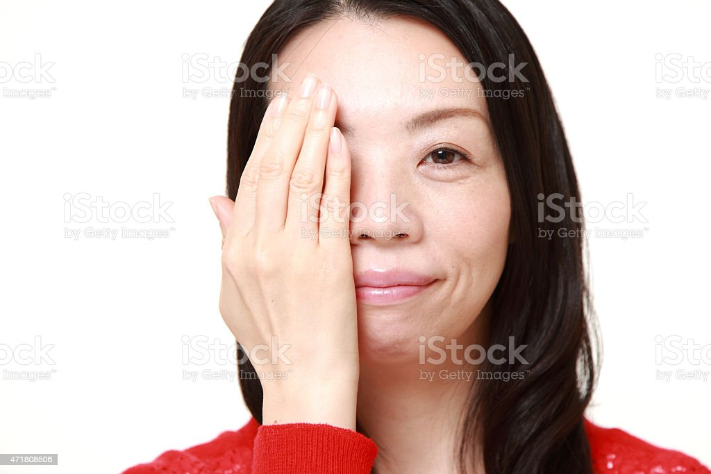 Japanese woman covering one eye with her hand stock photo