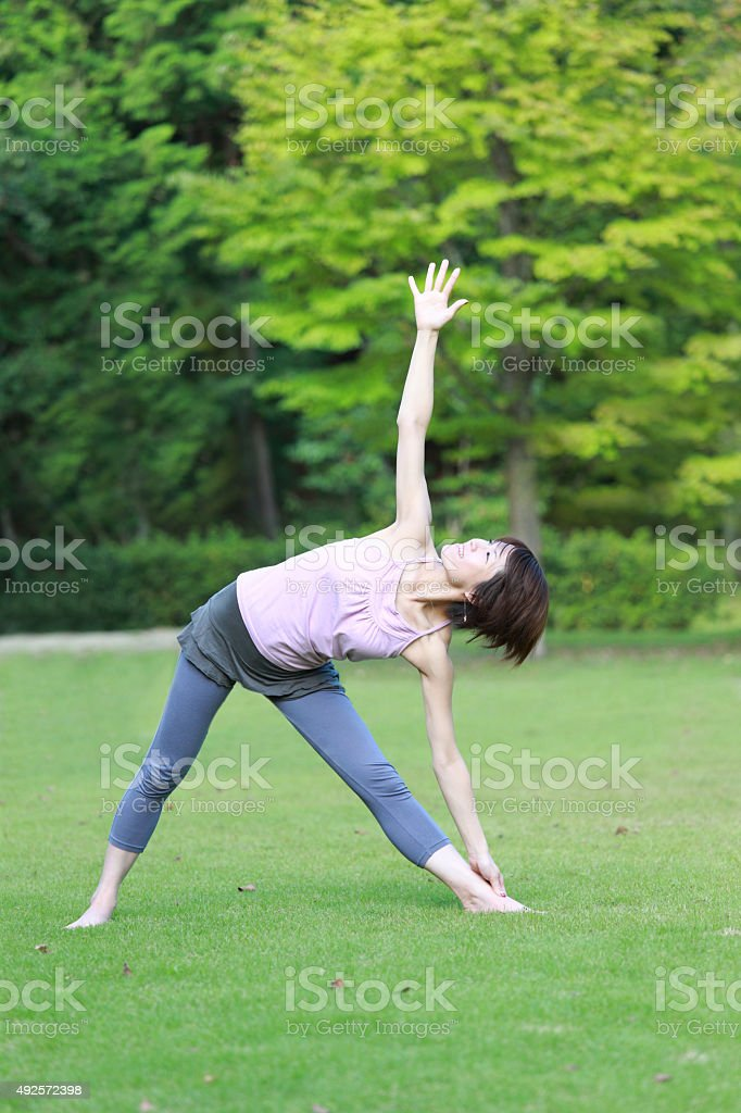 Japanese Woman Doing YOGA 'extended triangle pose' stock photo