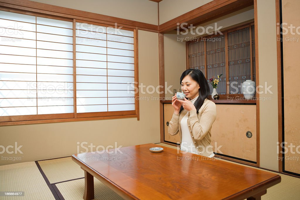 Japanese Woman Drinking Tea in Traditional Home royalty-free stock photo