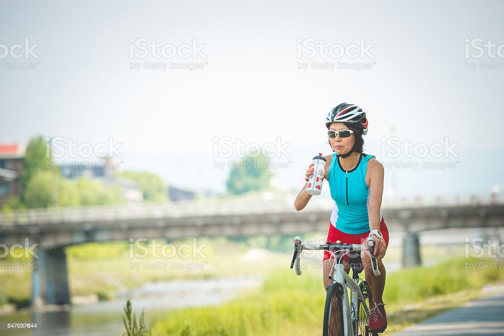 Japanese Woman Drinking Water while Riding Bike, Kamo River, Kyoto stock photo