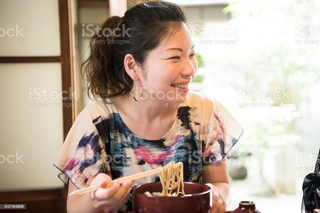 Japanese woman eating noodles with chopsticks, looking away stock photo