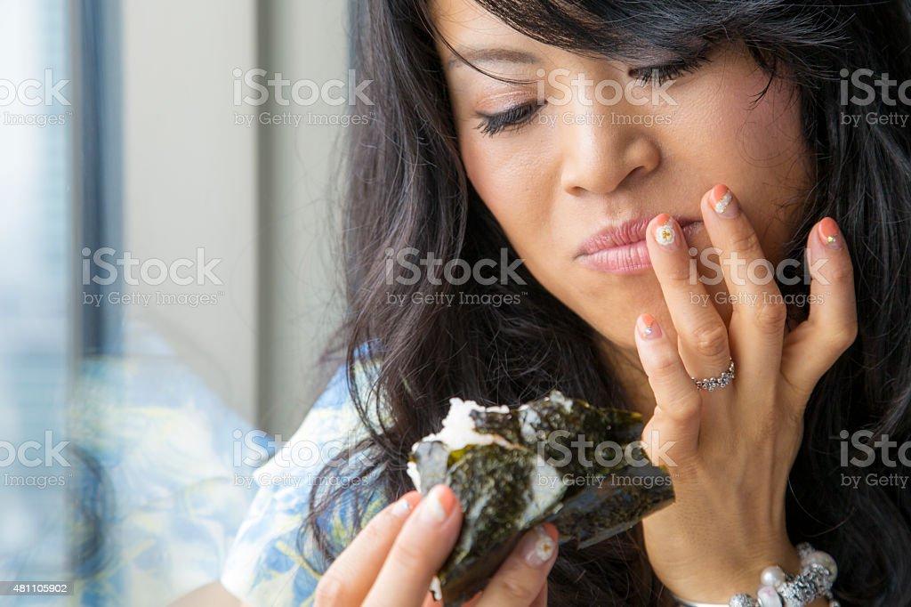 Japanese woman eating Onigiri stock photo
