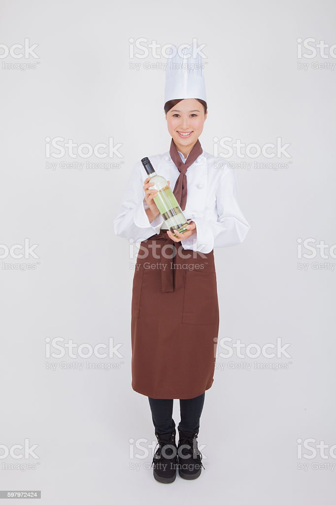 Japanese woman in chef's uniform holding wine stock photo
