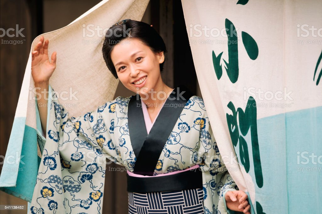 A smiling Japanese woman looks out through noren curtains outside her...
