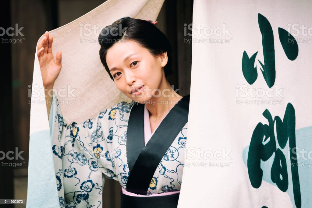 A Japanese woman looks out through noren curtains outside her shop....