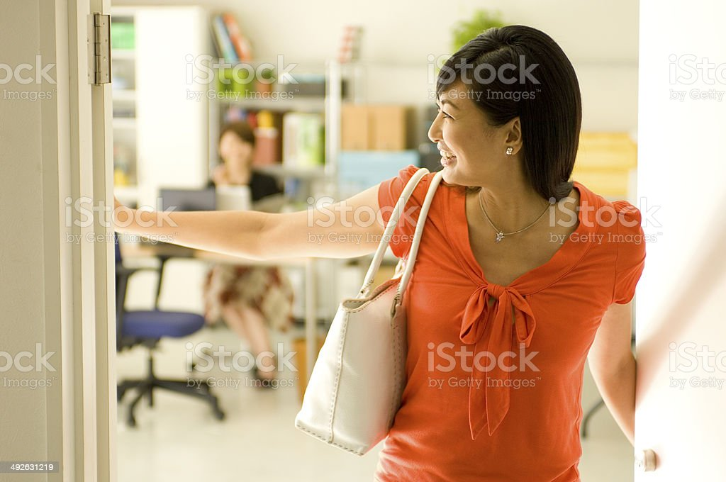 Japanese woman in her twenties coming out of office stock photo