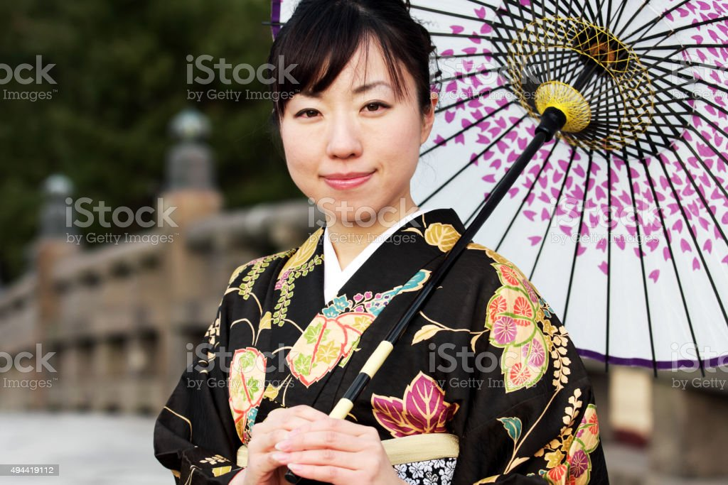 Japanese woman in kimono and with umbrella looking at camera stock photo
