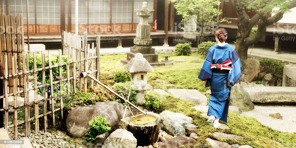 Japanese woman in kimono walking in temple garden panorama stock photo