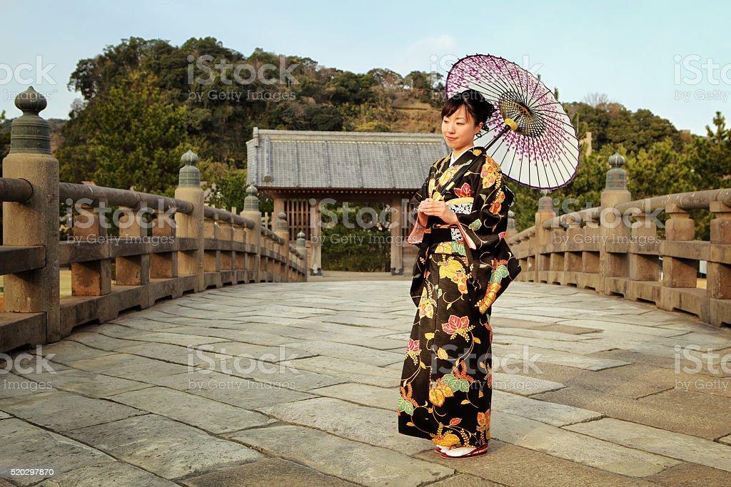 Japanese woman in kimono with umbrella at bridge stock photo