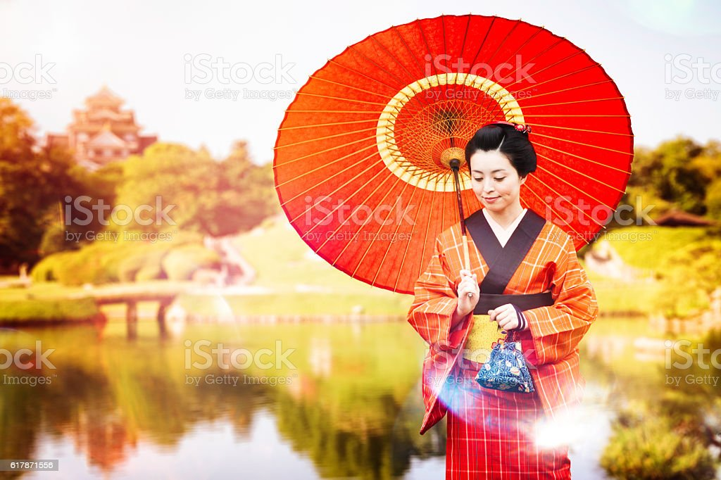 Japanese woman in red kimono and umbrella walking in park stock photo
