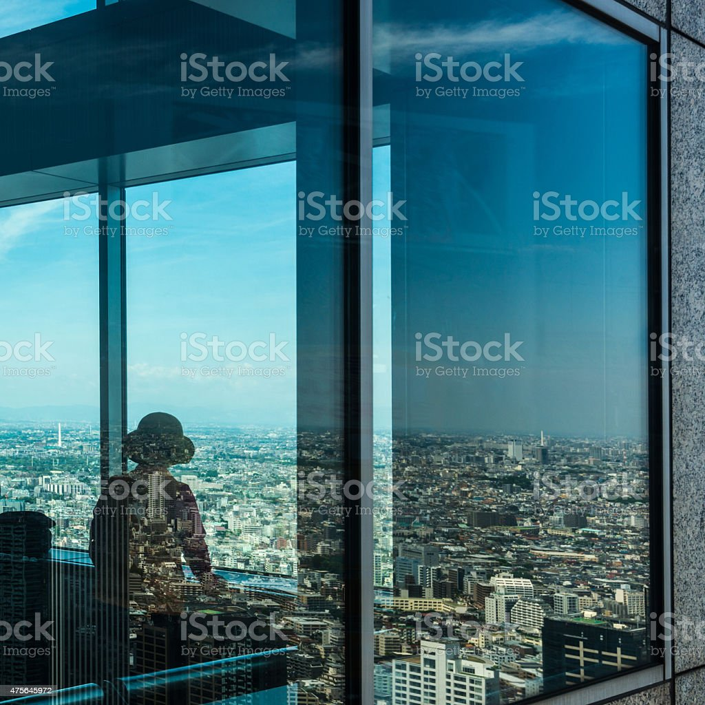 Japanese woman in Tokyo looking at the city stock photo