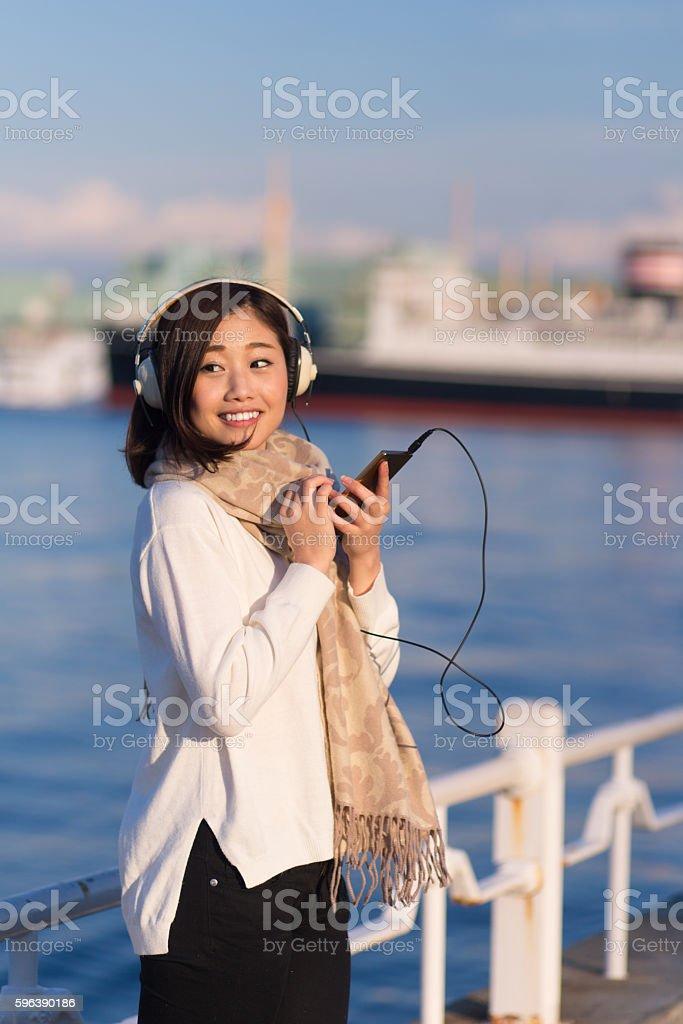 Japanese woman listening to music on harbor stock photo