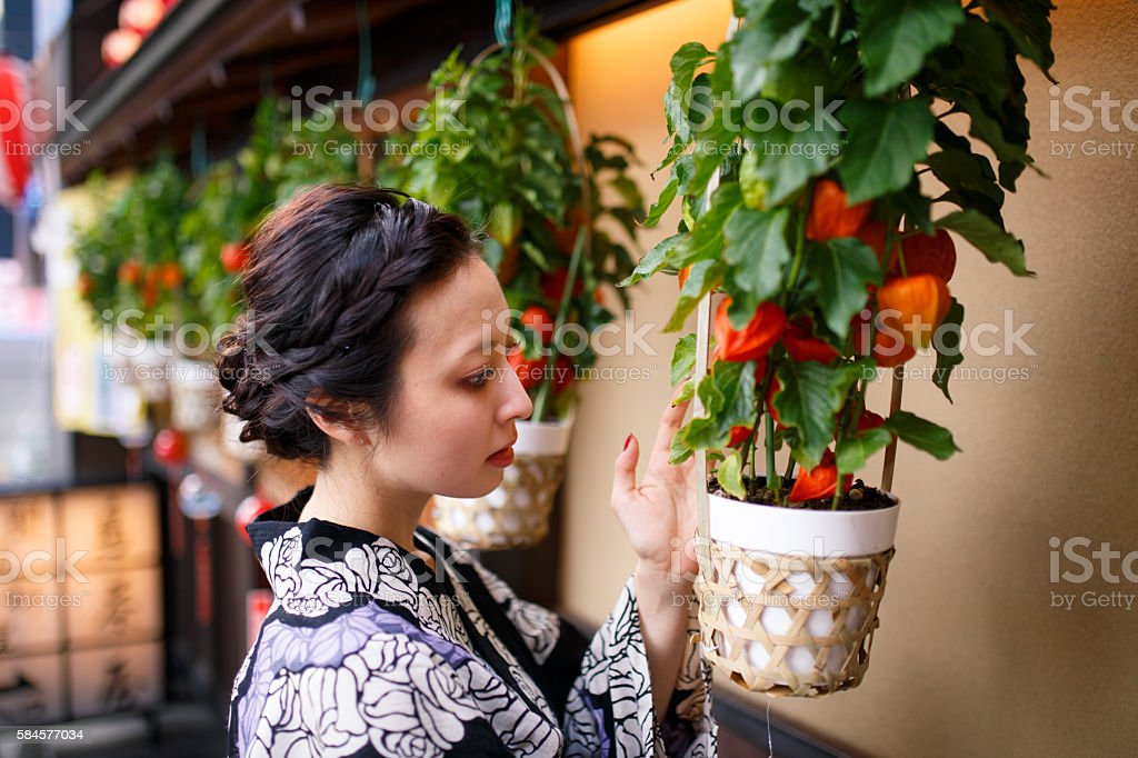 Japanese woman looking at houzuki ground cherry stock photo