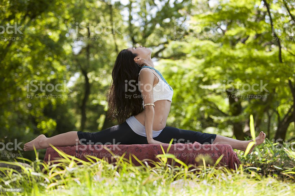 Japanese woman looks up while doing a yoga pose royalty-free stock photo