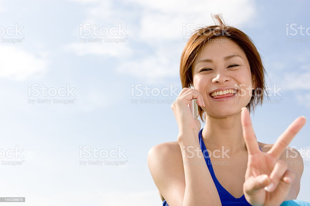 Japanese woman making a peace sign royalty-free stock photo