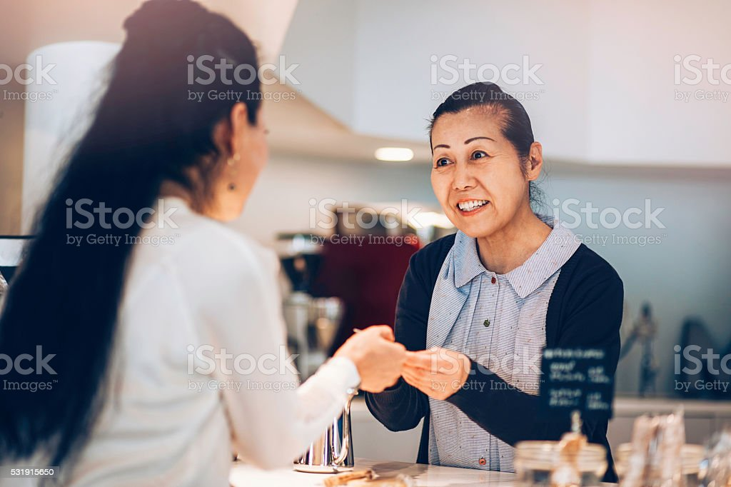 Japanese woman making payment with credit card in cafe stock photo
