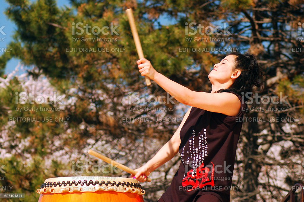 Japanese Woman performs Traditional Taiko Drumming stock photo