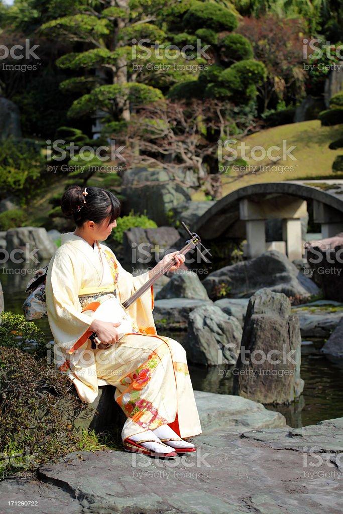 Japanese woman playing shamisen in garden stock photo
