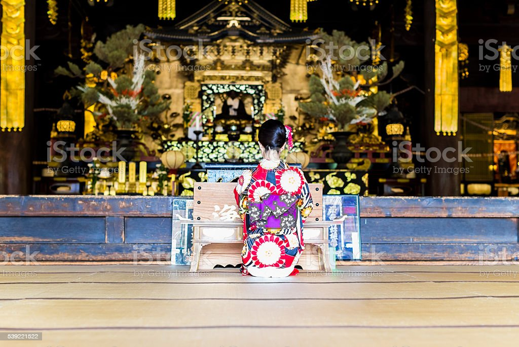 Japanese woman praying at a temple stock photo