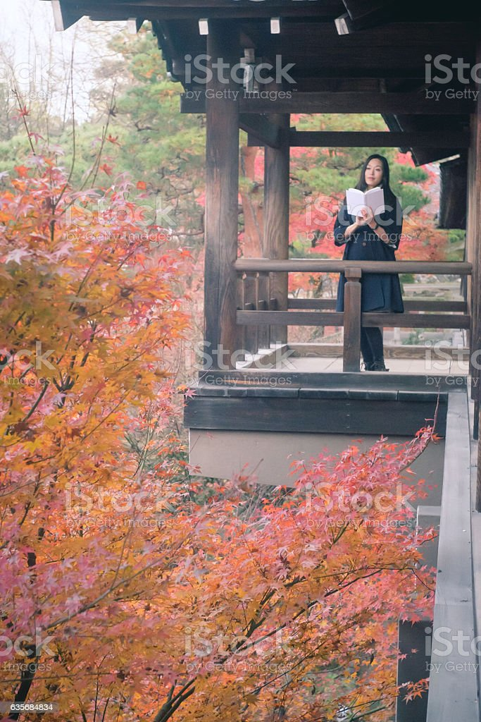 Japanese woman reading book at Tuutenkyo, Tofukuji-Temple, Kyoto stock photo