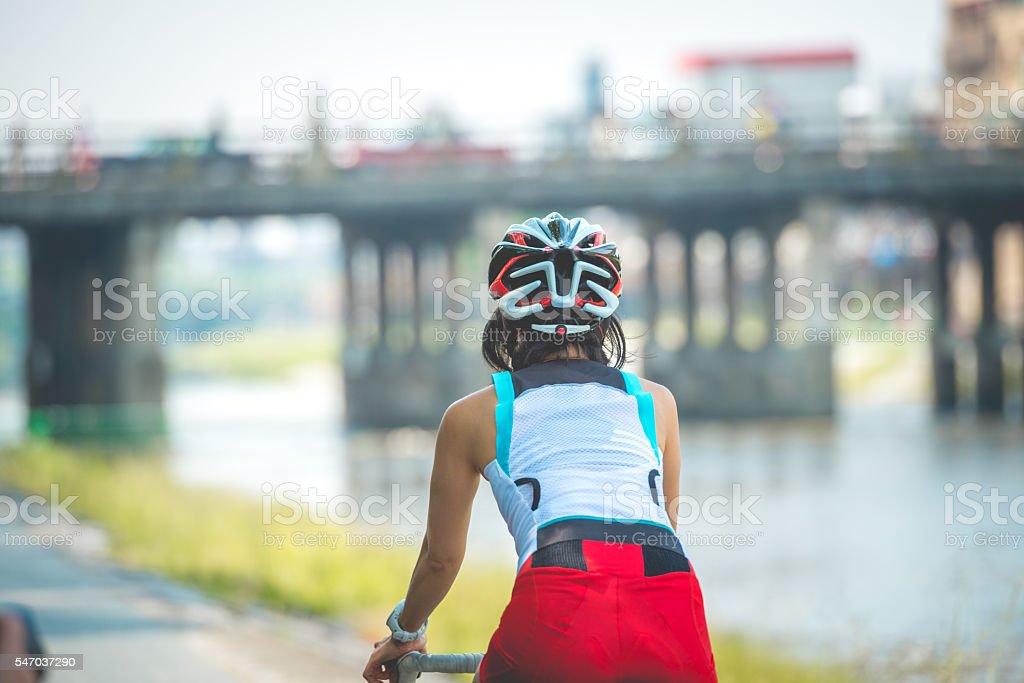Japanese Woman Riding a Bike by Kamo River, Kyoto, Japan stock photo