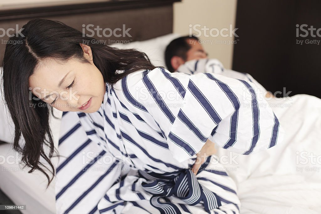 Japanese woman sitting on bed suffering back pain stock photo
