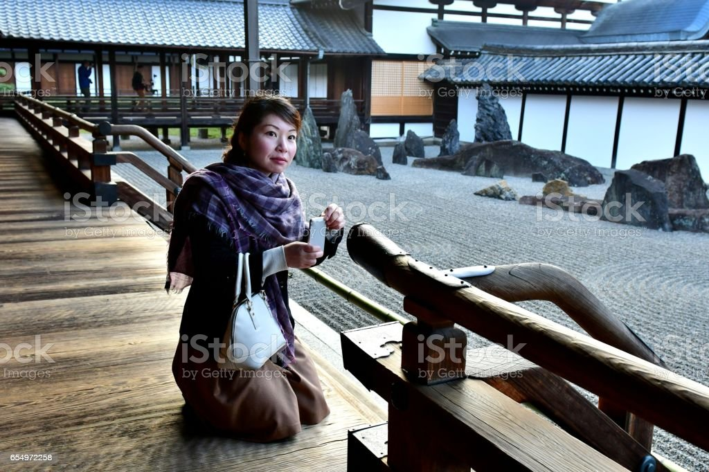 Japanese Woman Taking Photograph of Rock Garden at Tofuku-ji, Kyoto stock photo